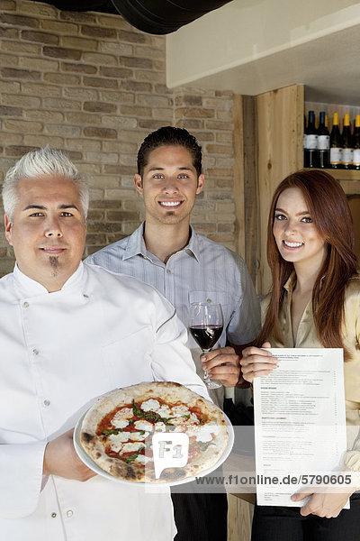 Porträt von glücklich Chef halten Pizza mit junges Paar