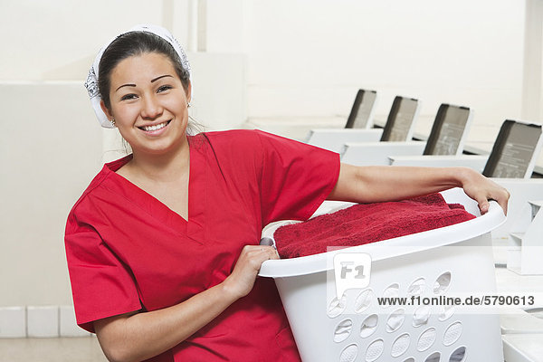Portrait of a happy young female employee carrying laundry basket