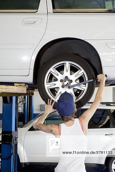 Rückansicht des jungen weiblichen arbeiten auf Pkw-Reifen in der Werkstatt