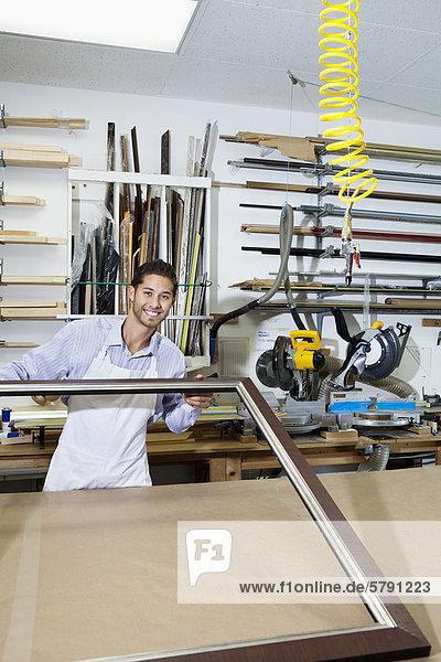 Porträt von einem freudig Handwerker arbeiten bei Bilderrahmen