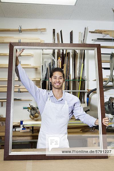 Porträt der glückliche junge Handwerker halten große Frame in der Werkstatt