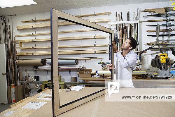 Junge Handwerker  die Konzentration auf das machen von Bilderrahmen in Werkstatt