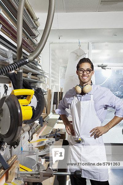 Porträt der Facharbeiter stehend mit den Händen an den Hüften in Werkstatt