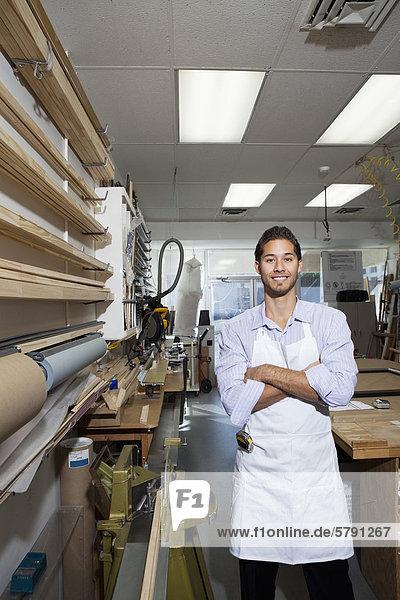 Porträt von glücklich Facharbeiter stehend mit Arme verschränkt in Werkstatt