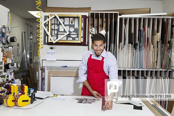 Porträt von glücklich Facharbeiter Messen mit Meter Stock in der Werkstatt