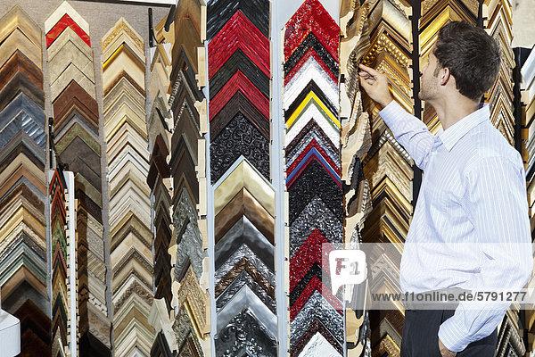Junger Mann  Blick auf Multi farbige Bilder im Speicher