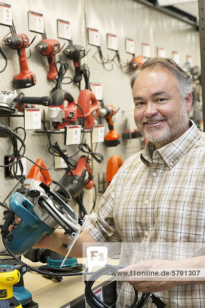 Portrait of a happy hardware store owner with electric saw