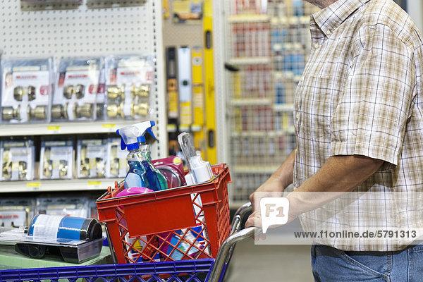 Mittelteil des Mannes mit Warenkorb im Baumarkt