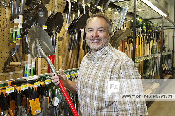 Portrait of a happy mature man holding shovel in hardware store