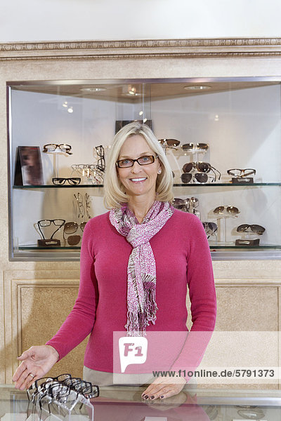 Portrait of a senior optometrist wearing glasses in store