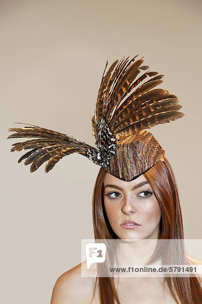Young woman wearing feathered headdress while looking away over colored background