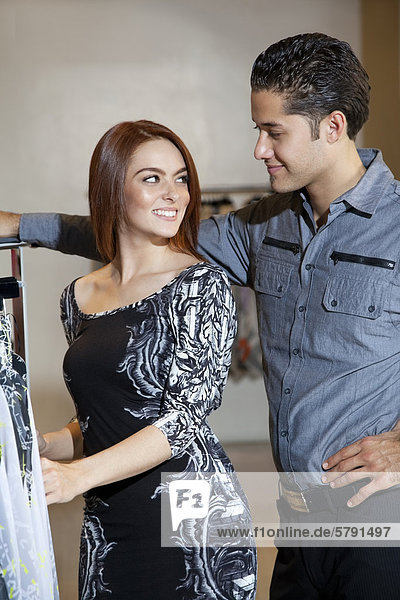 Happy young couple looking at each other while shopping in fashion boutique