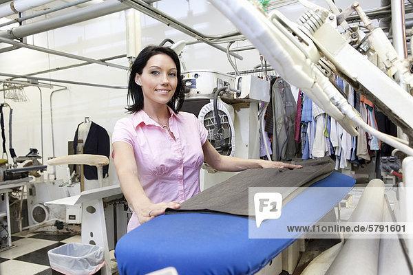 Porträt von einem glücklichen Mitte erwachsen frau maschinell Bügeln Wäsche