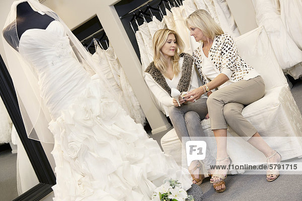Tilt shot of mother and daughter sitting with footwear in bridal store
