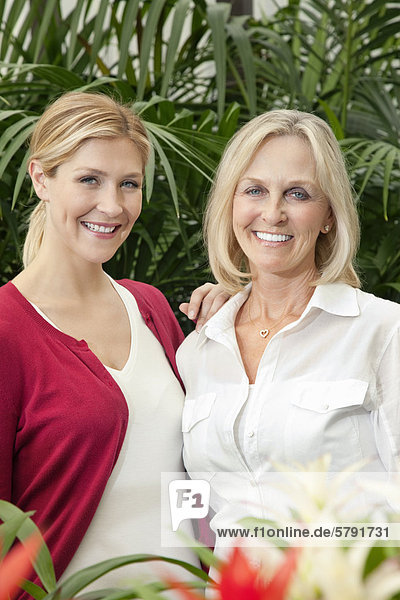 Portrait of cheerful mother and daughter in garden