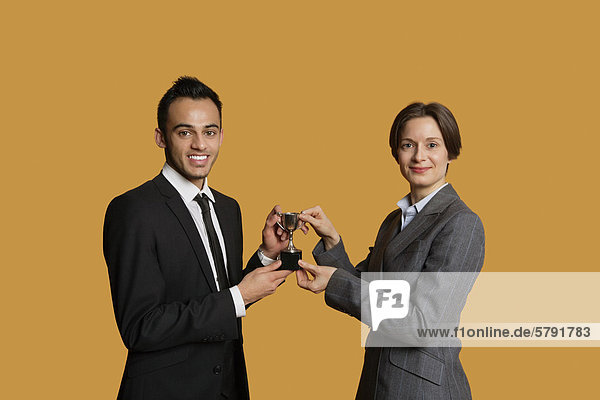 Portrait of happy partners holding winning trophy together