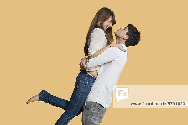 Side view of young couple looking at each other while man carrying girlfriend over colored background