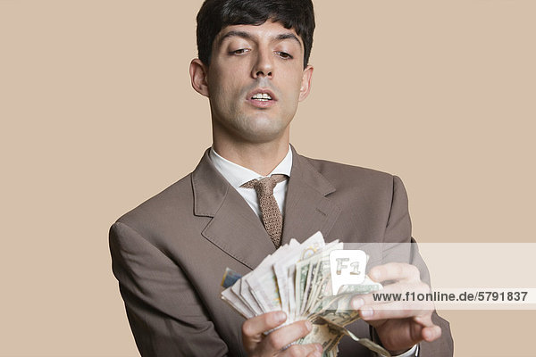 Young businessman counting money over colored background
