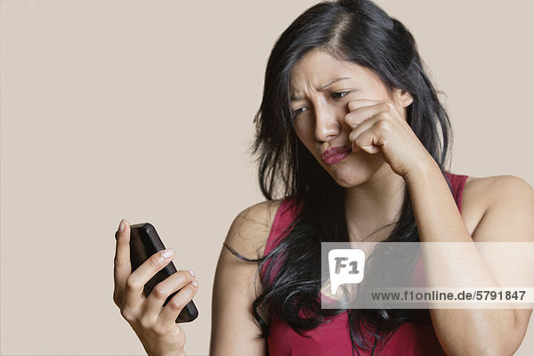 Sad young woman looking at mobile phone over colored background
