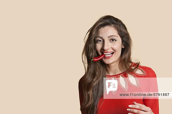 Porträt einer schönen jungen Frau mit Roter Chili in Mund über farbigen Hintergrund