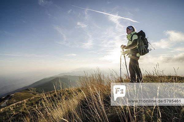 Wanderin  Frau Anfang 40  steht bei Sonnenuntergang am Col Visentin  Italien  Europa