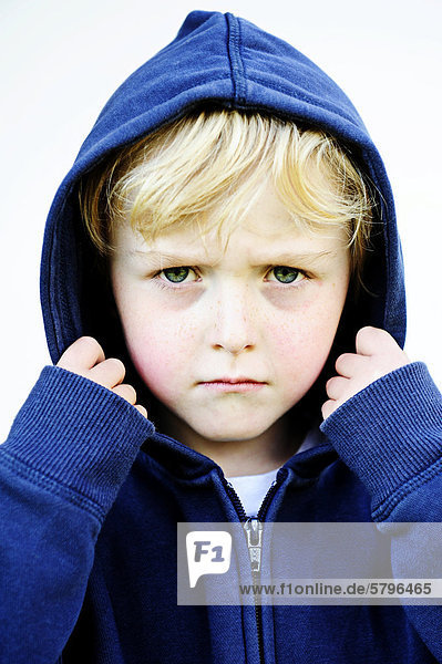 5-jähriger Junge mit Kapuzenjacke schaut grimmig  Portrait