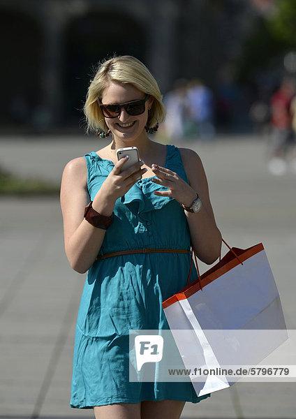 Junge Frau mit Handy  beim Shopping  Shoppen  Einkaufen  Königsstra_e  Stuttgart  Baden-Württemberg  Deutschland  Europa  ÖffentlicherGrund