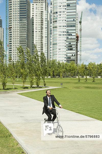 Geschäftsmann auf dem Fahrrad im Park