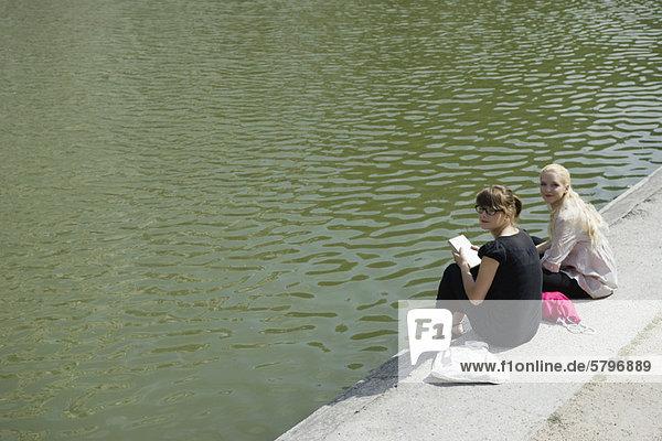 Junge Frauen sitzen zusammen am See.