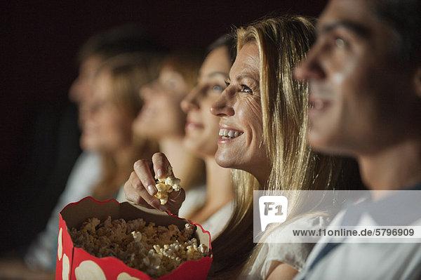 Frau isst Popcorn  während sie sich im Theater einen Film ansieht.