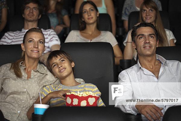 Familie genießt Film im Theater  Junge ruht Kopf auf der Schulter seiner Mutter