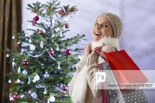 Frau mit Einkaufstaschen  Weihnachtsbaum im Hintergrund