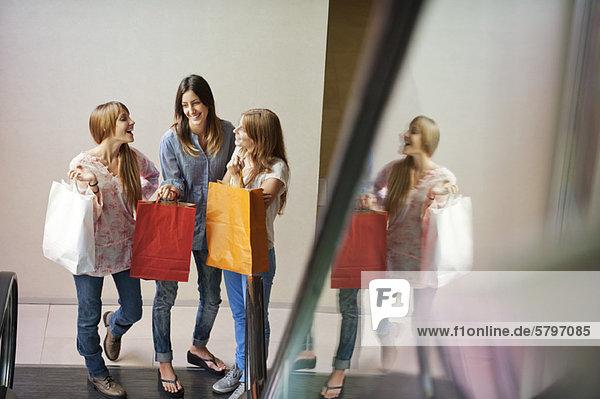 Junge Frauen mit Einkaufstaschen  unten an der Rolltreppe stehend Junge Frauen mit Einkaufstaschen, unten an der Rolltreppe stehend