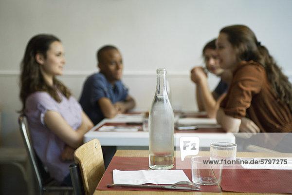 Freunde  die im Café abhängen  konzentrieren sich auf den leeren Tisch im Vordergrund.