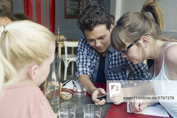 Freunde  die zusammen im Café rumhängen und sich das Handy ansehen.