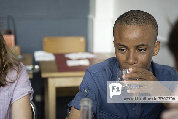 Junger Mann bei einem Drink im Café