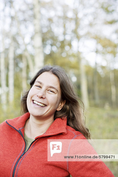 Portrait of cheerful woman in woods