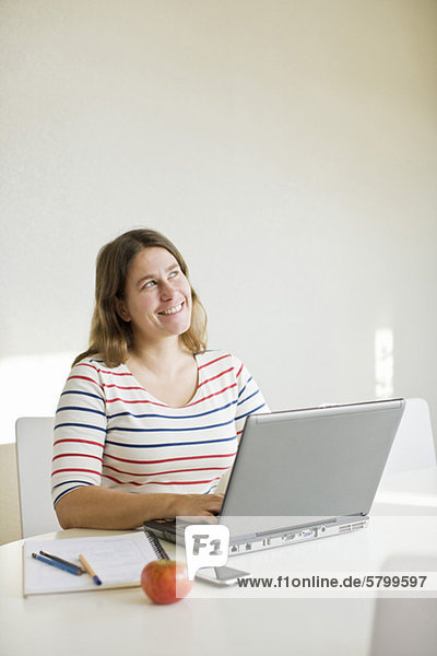 Fröhliche mittlere erwachsene Frau  die weg schaut  während sie den Laptop benutzt.