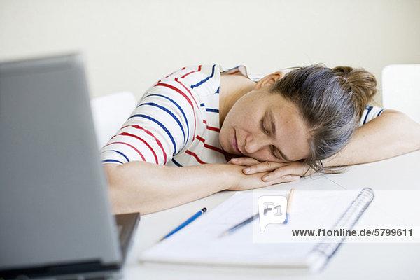 Erschöpfte mittlere erwachsene Frau schläft am Tisch mit Laptop