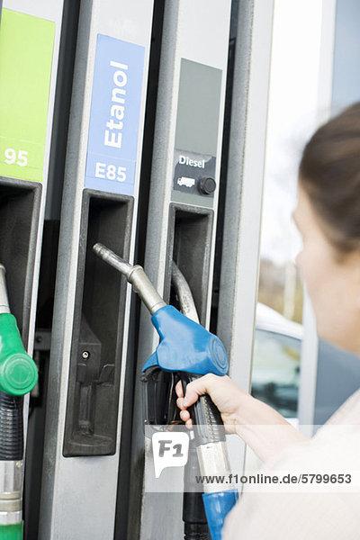 Frau hält eine Kraftstoffpumpe an der Tankstelle.