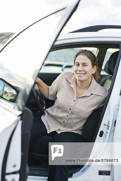 Porträt einer glücklichen erwachsenen Frau,  die aus dem Auto steigt.