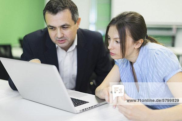 Geschäftskollegen arbeiten gemeinsam am Laptop im Büro