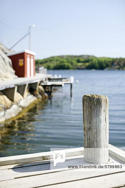 Holzpfosten der Mole im See