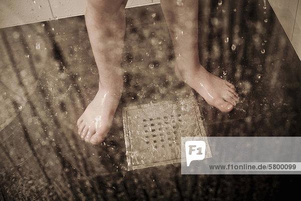 Niedriger Abschnitt eines Jungen  der im häuslichen Badezimmer am Abfluss steht.