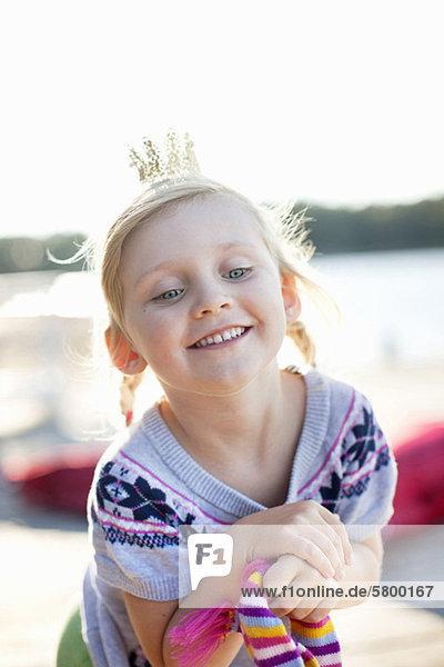 Fröhliches Mädchen mit Krone lächelnd im Freien Fröhliches Mädchen mit Krone lächelnd im Freien