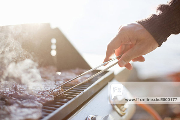 Close-up of man flipping beef with tongs on barbecue grill