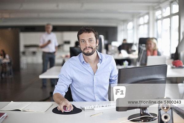 Portrait eines Geschäftsmannes mit Computer im Büro
