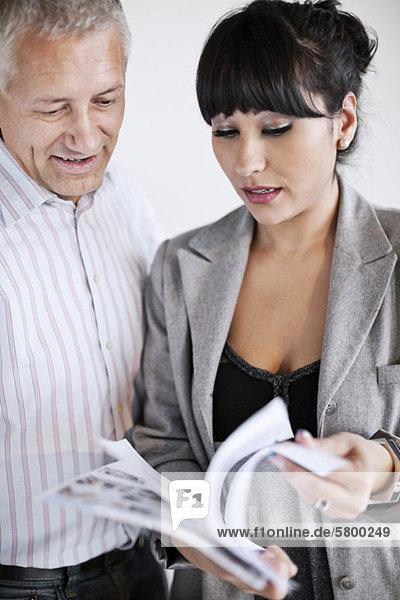 Geschäftsmann und Geschäftsfrau bei der Prüfung von Dokumenten