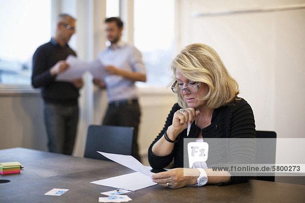 Geschäftsfrau beim Lesen mit Kollegen im Hintergrund