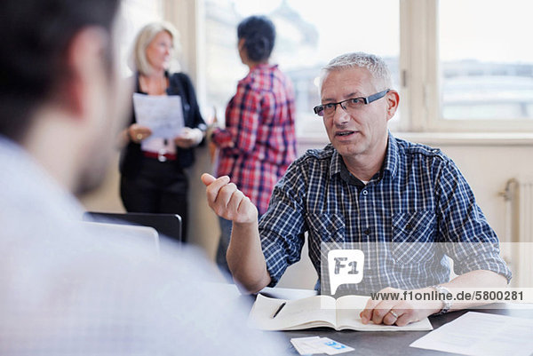 Mature businessman discussing with male colleague and businesswomen in background